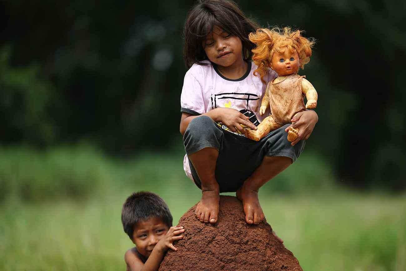 Crianças guaranis-caiovás brincam em acampamento ao lado da BR-463, onde é comum a ocorrência de atropelamentos de indígenas e outros assentados que vivem ao longo da estrada. Foto: Dida Sampaio, Estadão